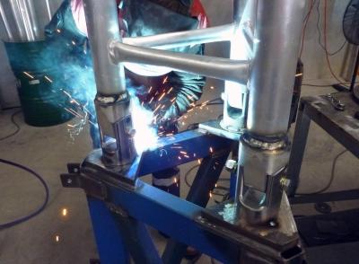 AL500 tripod tower hinges being welded
